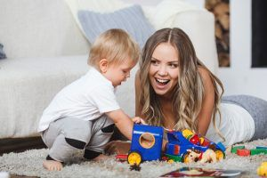 cute blonde mother and child boy play together indoors at home on the carpet